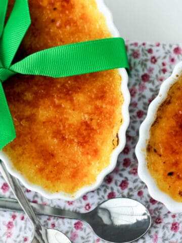 2 French Crèmes brûlées in a white dish with a green ribbon in a bow and 2 spoons on the side