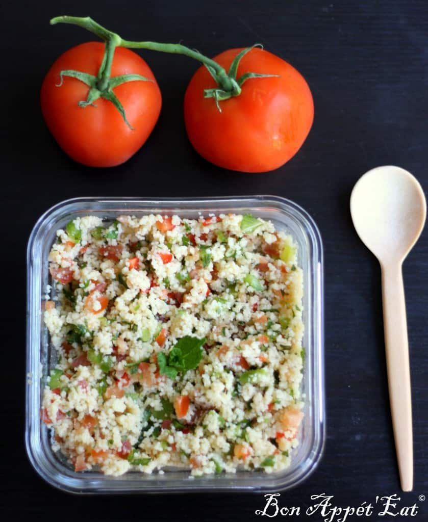 tabouleh in a square container with a wooden spoon and 2 tomatoes on the side