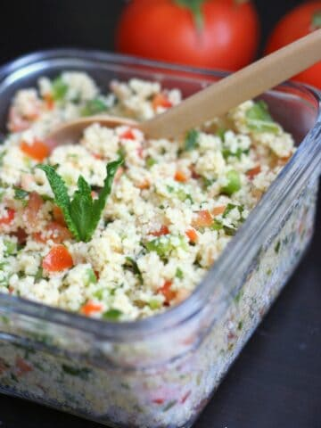 tabouleh in a square container with a wooden spoon