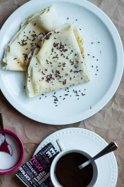 view from top of 2 crepes folded with chocolate sprinkles with a cup of dark coffee on the side and a ramekin of sugar.