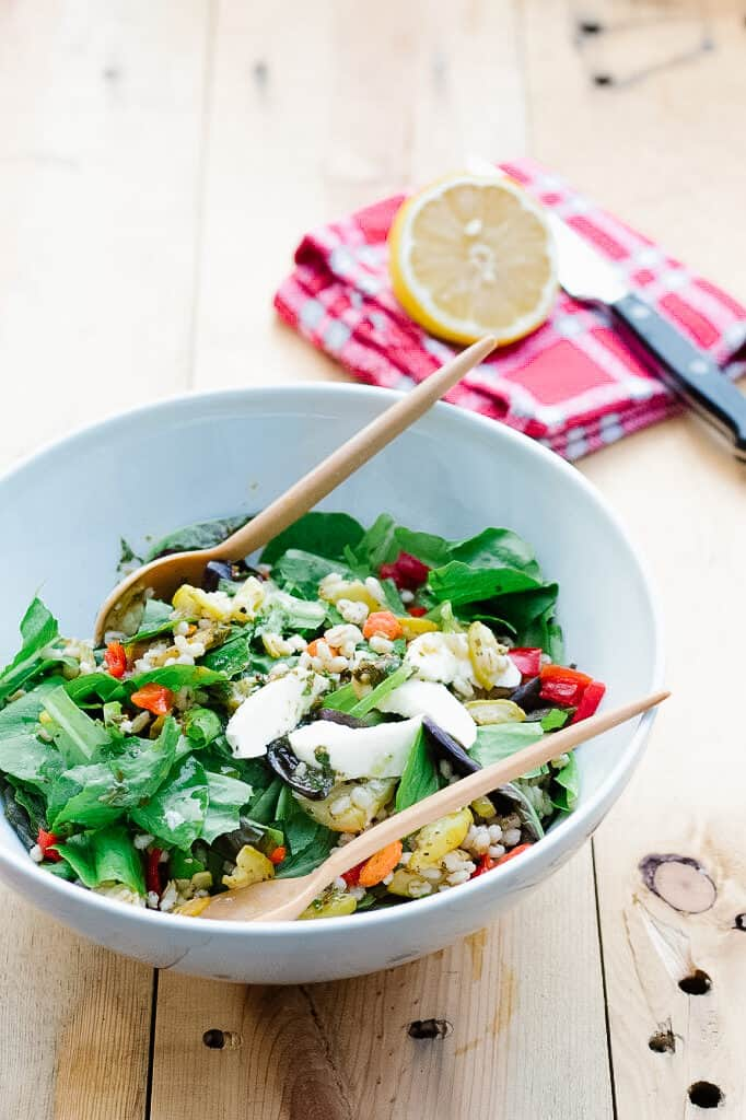 White bowl with veggie salad and wooden cutlery in. Lemon and red napkin on the side