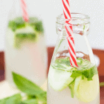 Picture of 2 small bottles with red straws with a lime, mint and cucumber floating
