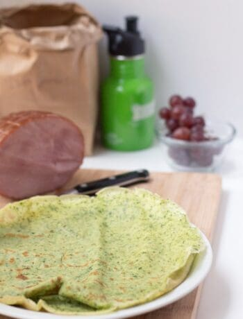 Side picture of savory crepes, green with grapes in the back and some ham.