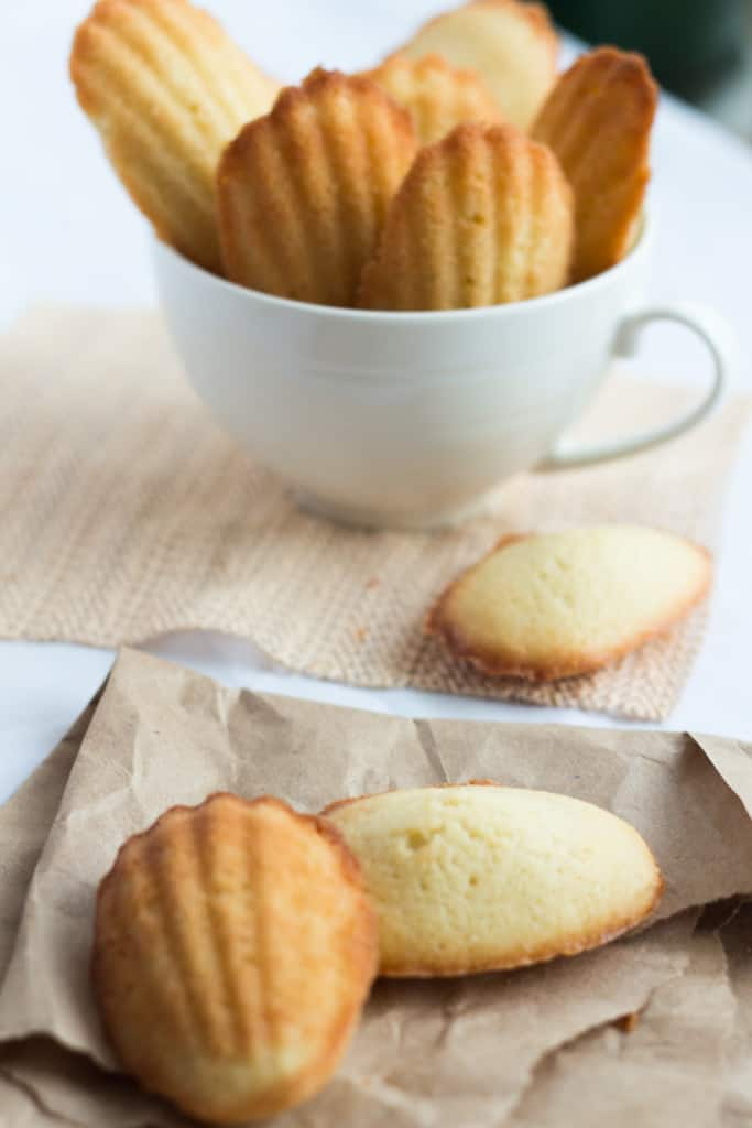 Madeleine Recipe: Madeleines in a white cup and some more around and brown paper