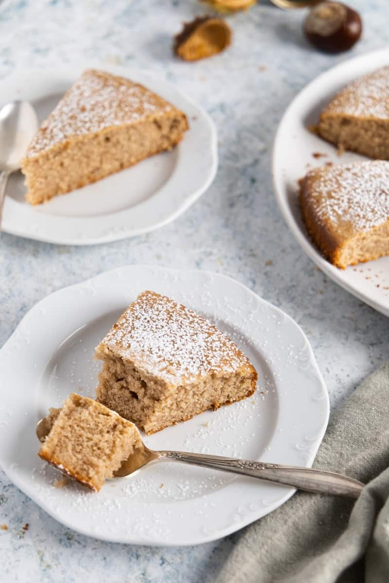 Two small white plates with a slice of chestnut cake each. One has a spoon with some cake in it.