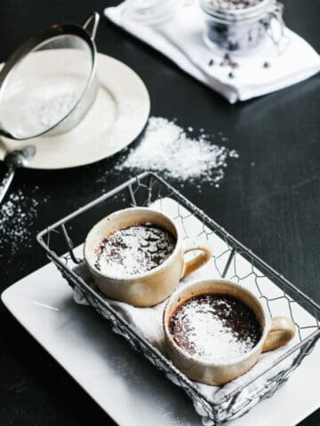 Cup filled with chocolate pot de creme and spoon picking some.