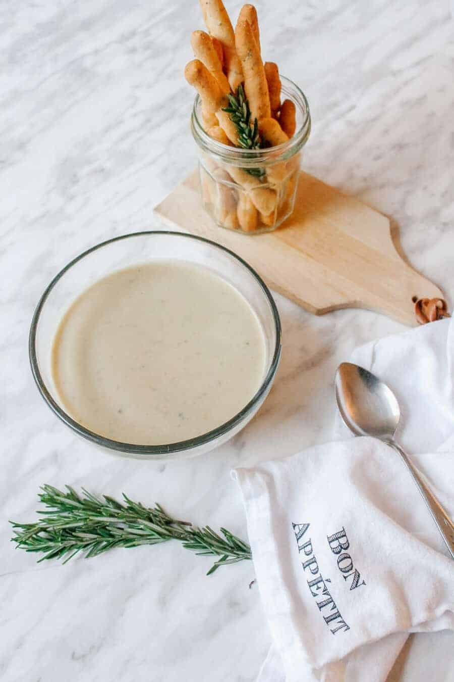 Bowl of French rosemary potato leek soup with bread sticks