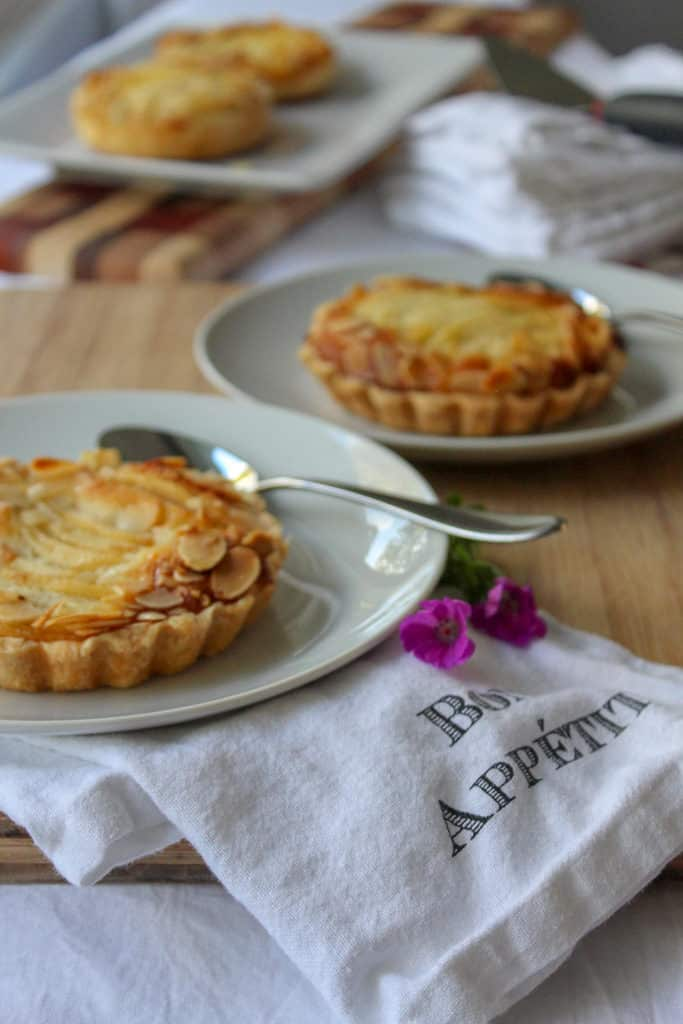 Two small tarts Amandine in plates: a delicious flaky crust with an almond cream filling and a juicy pear.
