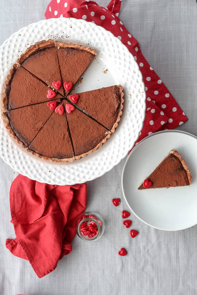 View from above of a sliced dark French chocolate tart on a shortbread crust.