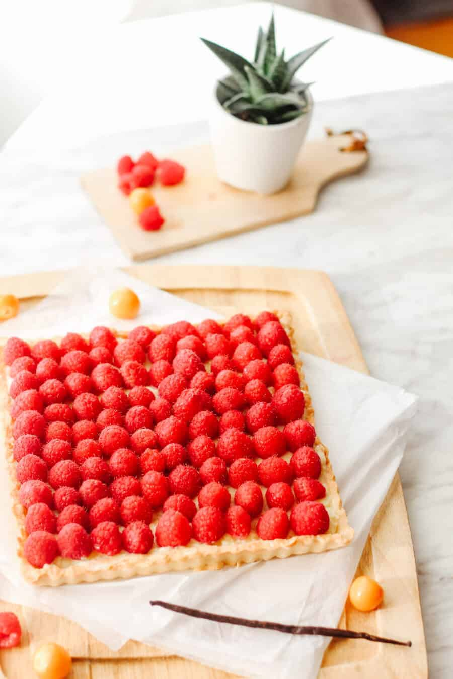 Side view of a raspberry tart with french vanilla pastry cream filling