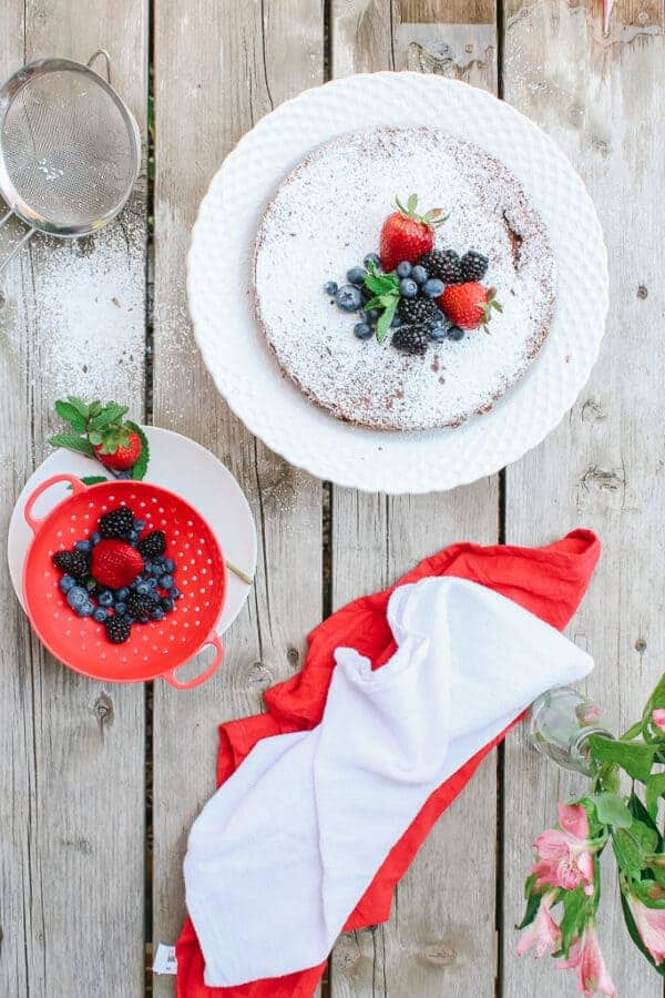 Top view of chocolate cake with berries on the side. White and red dish clothes