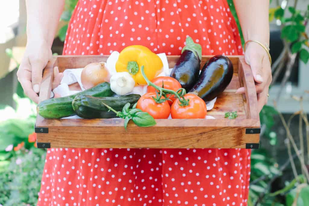 Person with a red polka dot dress holding a wooden tray with a bouquet of flowers and different vegetables: 3 tomatoes, 2 zucchinis, yellow pepper, onion, garlic