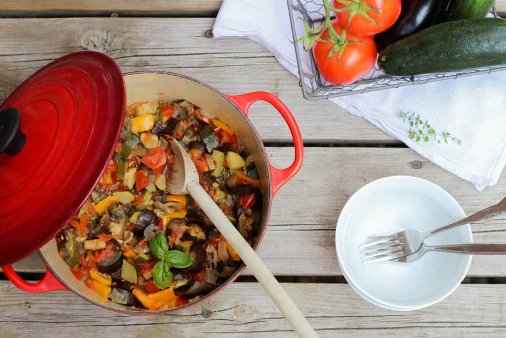Big red one pot full of easy French ratatouille with a white bowl on a wood background