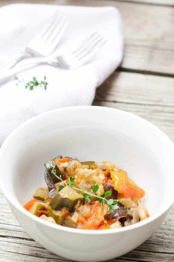 White bowl with easy french ratatouille on a wood background