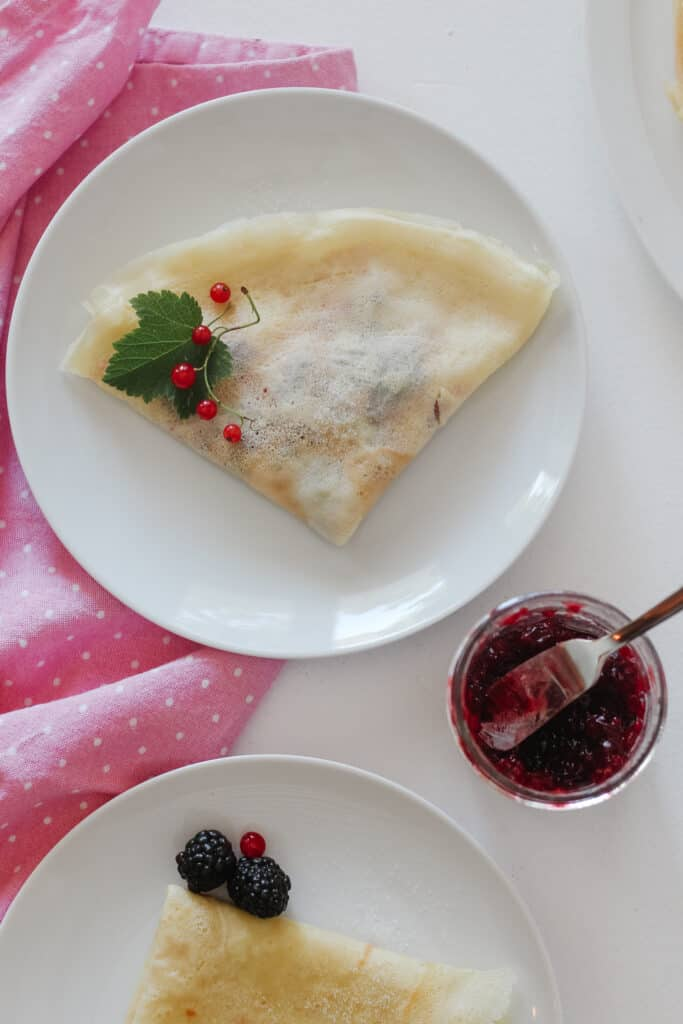 View from above, 2 plates with a folded Oat milk French crêpes, a jar of jam and a pink dish towel.