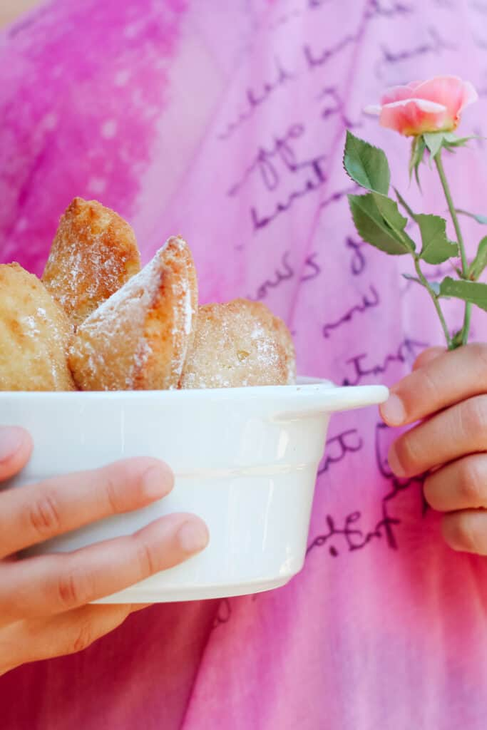 Hand holding a white dish filled with rose water French madeleines and a rose