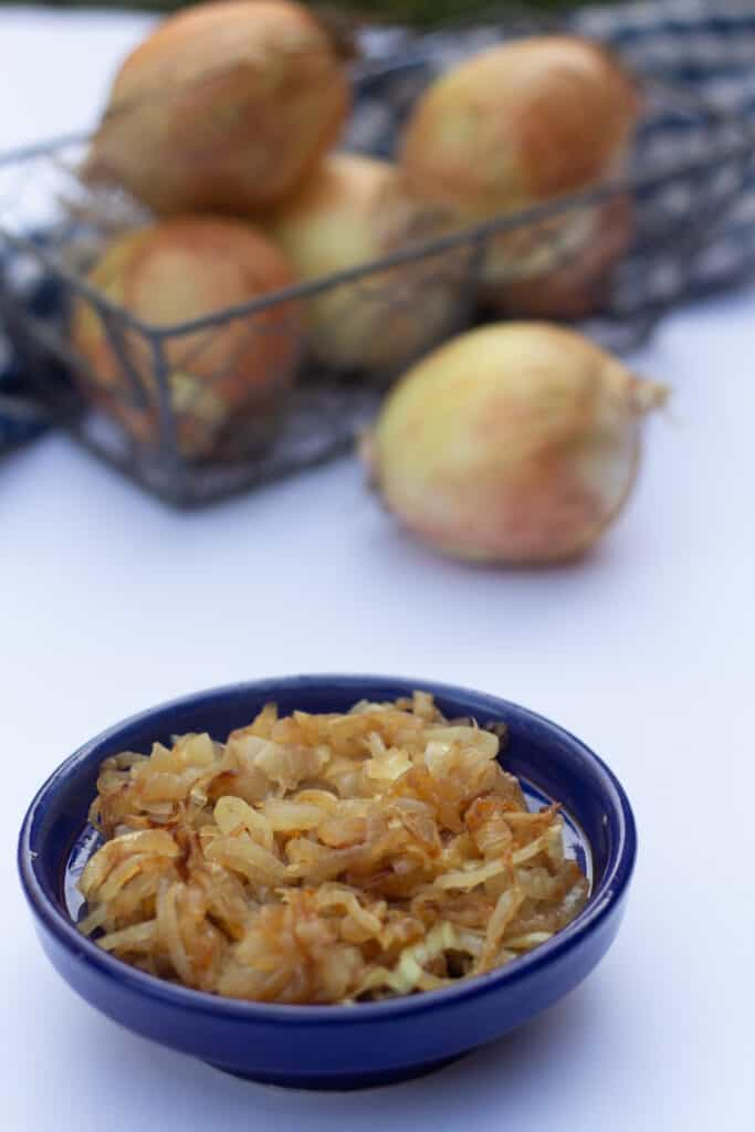 Caramelized onions with fresh onions in the background