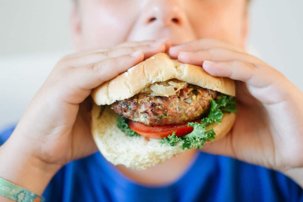 Kids hands holding an healthier ratatouille turkey burger and biting in it