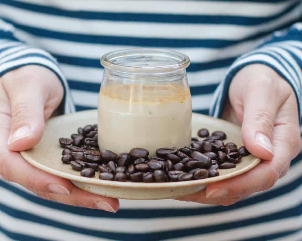 hands holding a small plate with a coffee pot de creme and whole coffee beans around, stripped top in the background