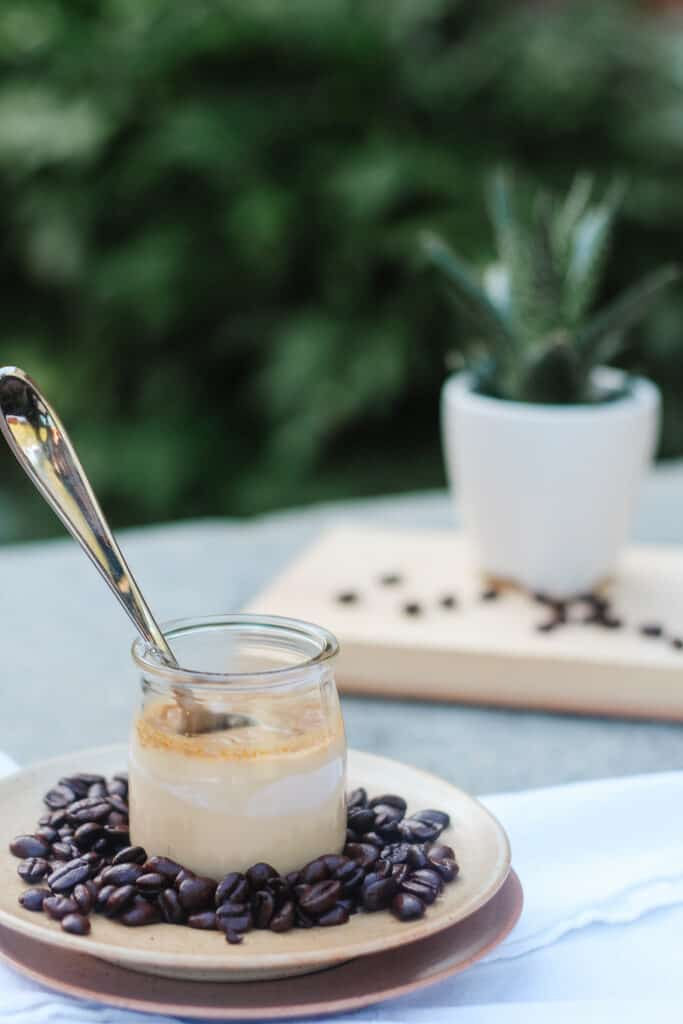 spoon in a coffee pot de creme with whole coffee beans around, stripped sleeve