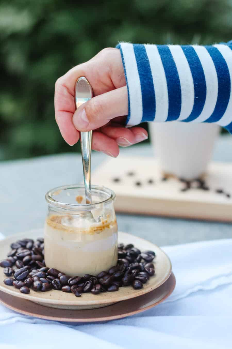 Hand scooping in a coffee pot de creme with whole coffee beans around, stripped sleeve