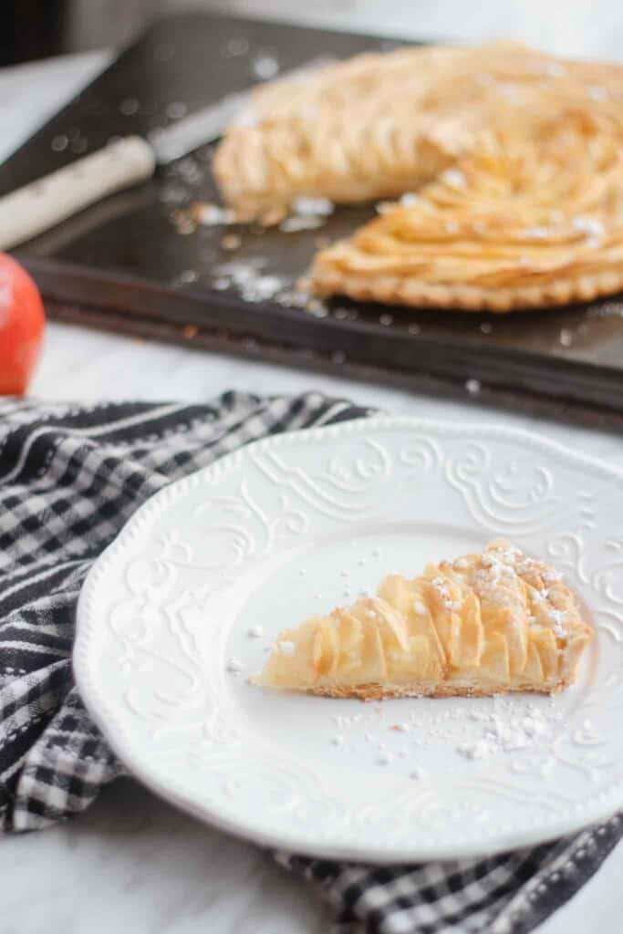 slice of the baked apple tart, black and white dish towel on the side.
