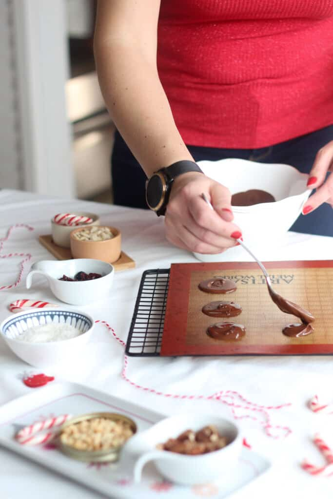 person in a red top preparing chocolate disks.