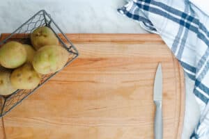 Wood Cutting board with potatoes and a knife.