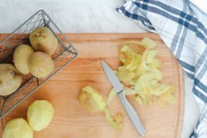 Peeling potatoes on a cutting board