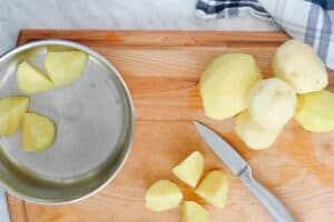 Cutting board with pot and potatoes being cut