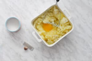 Square dish with mashed potatoes and egg yolks and butter