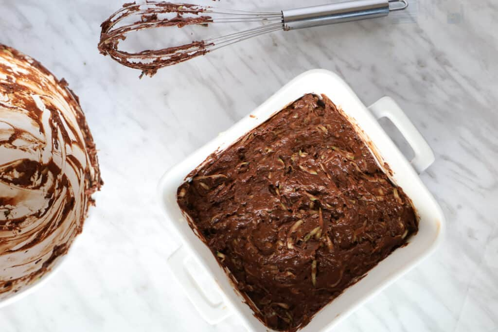 Chocolate Zucchini cake batter in a square white dish with a whisk on the side