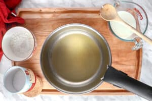 Melted butter in a pot with flour and a wooden spoon on the side