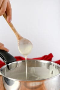Bechamel dripping from a wooden spoon