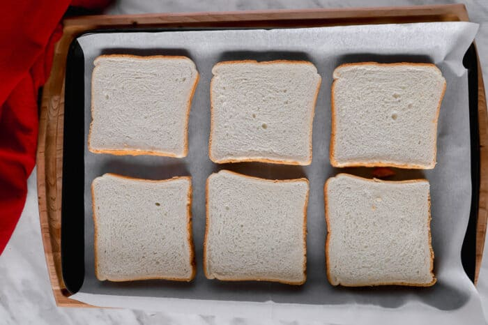 Bread slices on a baking sheet.