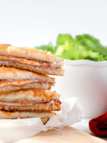 Stacked croque-monsieurs with a white bowl of salad in the back
