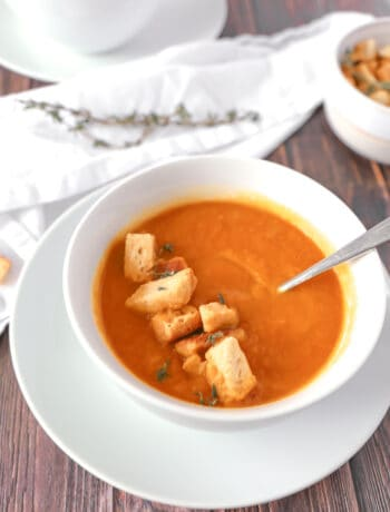 Close up of a carrot ginger soup in a white bowl with some croutons on top. Another bowl in the background with a white napkin.