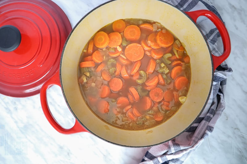 Cut carrots, celery, onions in a big pot with broth.
