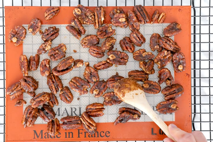 Caramelized pecans spread on a mat on a cooling rack