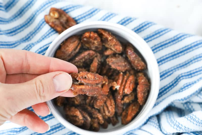 Bowl of caramelized pecans and a hand holding one.