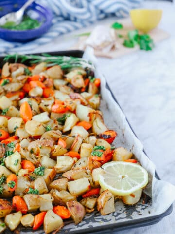 Side view of roasted carrots and potatoes in a baking sheet with a slice of lemon on the corner.