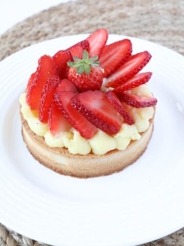 Individual serving of a strawberry pie in a white plate.