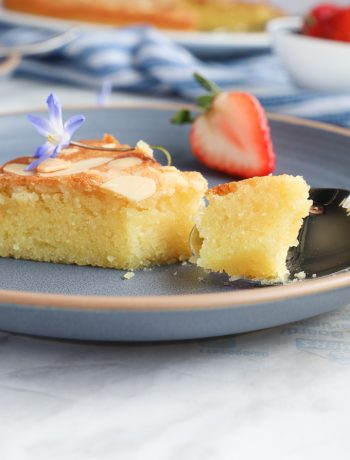 Slice of almond cake in a blue plate with a strawberry in the bake.