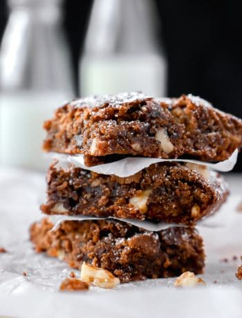 Side picture of a stack of gooey, fudgy almond flour brownies with 2 milk bottles in the back ground