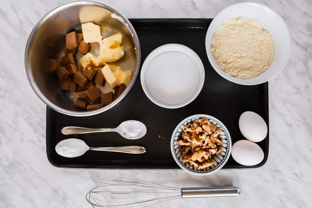 top view of ingredients for a chocolate brownies place on a black baking sheet.
