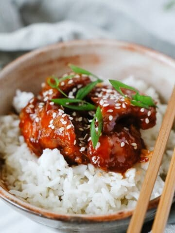 Close side view of 2 brown bowls with sweet and sour chicken served over white rice, some chop sticks on top