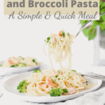 Side view of spaghetti with salmon and broccoli hanging from a fork.