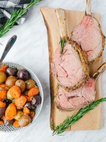 Cooked and cut in chop veal on a wooden baord, a dish full of potatoes on the side