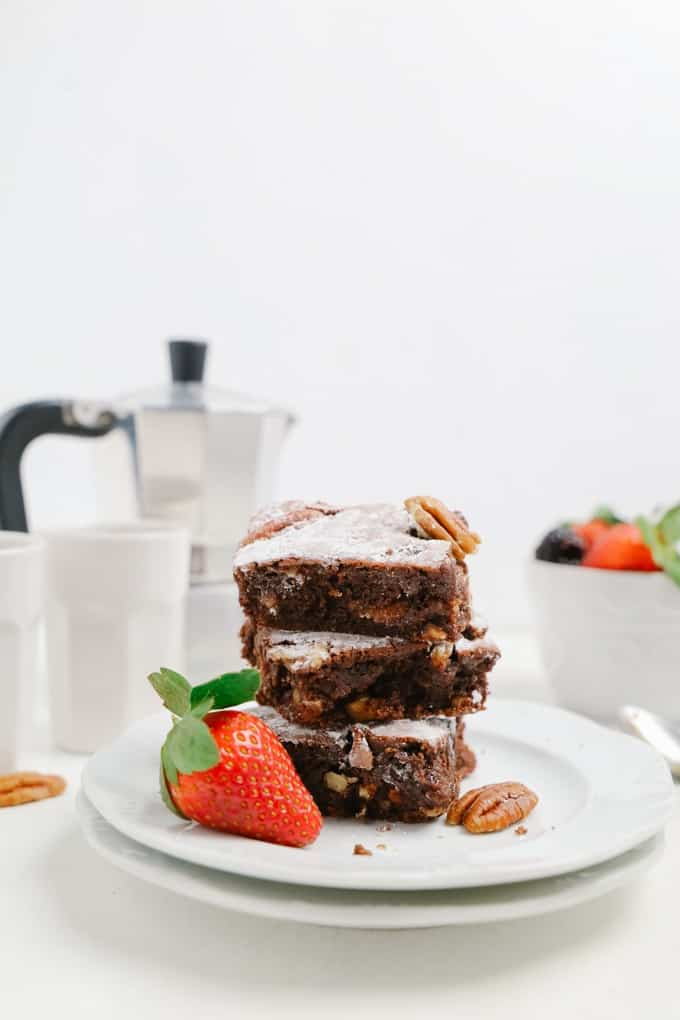 Side view of a stack of square brownies with a strawberry on the side and a coffee maker in the back