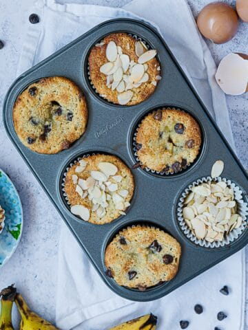 Top view of almond muffins cooked in a muffin tin. Ripe bananas on the side and egg shells.